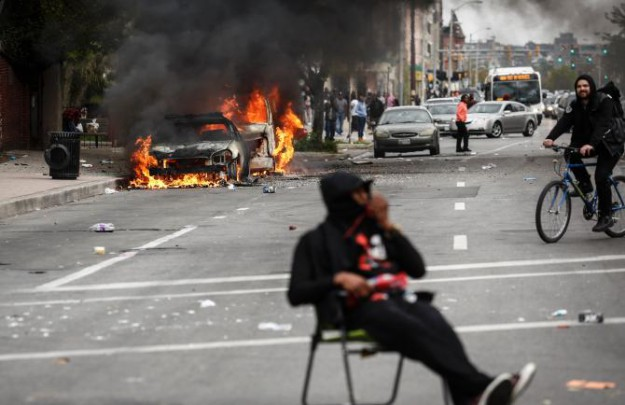 471375012-man-sits-in-the-street-near-burning-cars-near-the.jpg.CROP.rtstoryvar-large