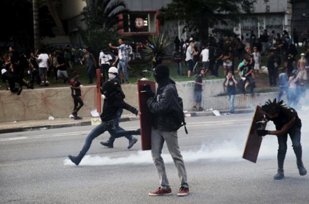 Demonstrator protester kicks a teargas canister fired by riot police during a protest against fare hikes for city buses in Sao Paulo